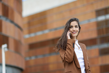 Young businesswoman talking with a smartphone in urban background. Beautiful woman wearing formal wear using smart phone.