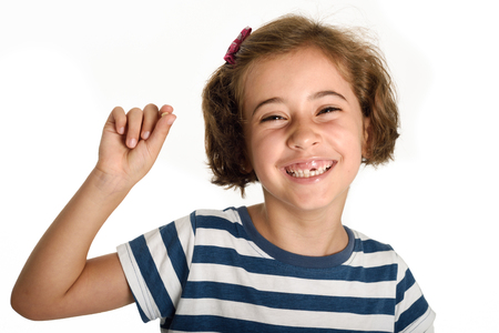 Happy little girl showing her first fallen tooth. Smiling little woman with a incisor in her hand. Isolates on white background. Studio shot. Stock Photo