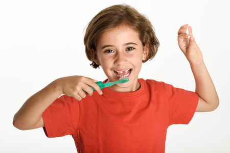 Happy little girl showing her first fallen tooth. Smiling little woman with a incisor in her hand brushing her teeth with a toothbrush isolates on white background. Studio shot. Stock Photo