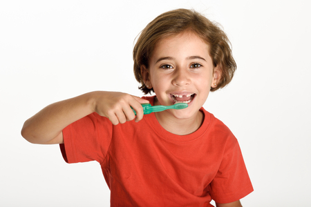 Happy little girl brushing her teeth with a toothbrush isolated on white background. Studio shot. Stock Photo