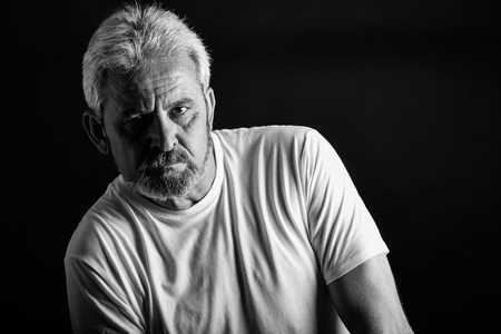 Portrait of a serious mature man looking at camera. Senior male with white hair and beard wearing casual clothes isolated on black background. Studio shot in black and white.