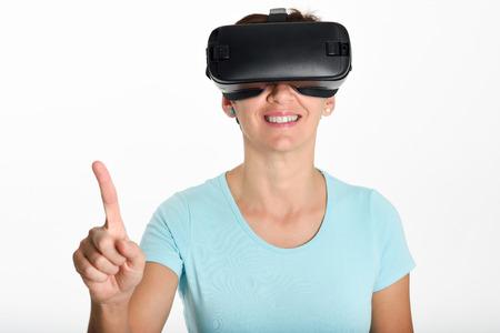Vrouw die in VR-glazen kijkt en met zijn handen gesturing. Mooi verrast wijfje die virtuele werkelijkheidsbeschermende brillen dragen die op films letten of videospelletjes spelen, die op witte achtergrond worden geïsoleerd. Stockfoto