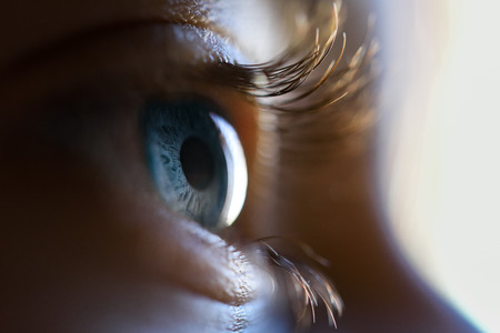 Close-up of beautiful little girl blue eye. Macro photograph.