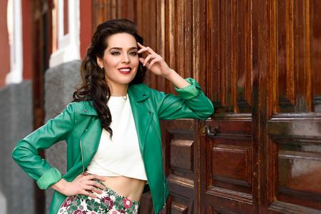Junge Brunettefrau, Modell der Mode, grüne moderne Jacken- und Blumenhosen tragend. Recht kaukasisches Mädchen mit dem langen gewellten Frisurlächeln. Frau mit den roten Lippen im städtischen Hintergrund.