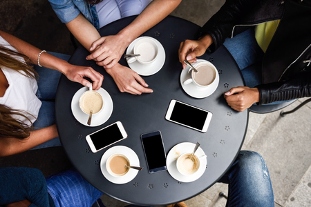 Top view of hands with coffee cups and smartphones on table in a urban cafe.