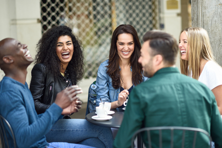 Groupe multiracial de cinq amis prenant un café ensemble. Trois femmes et deux hommes au café, discutant, riant et profitant de leur temps. Concepts de mode de vie et d'amitié avec des modèles de personnes réelles