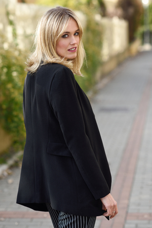 Beautiful blonde woman in urban background. Young girl wearing black blazer jacket standing in the street. Pretty female with straight hair hairstyle and blue eyes.