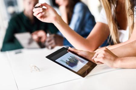 Jonge vrouw studeren met tabletcomputer op wit bureau. Mooie meisjes en jongens die samenwerken met casual kleding. Medewerkers groep.