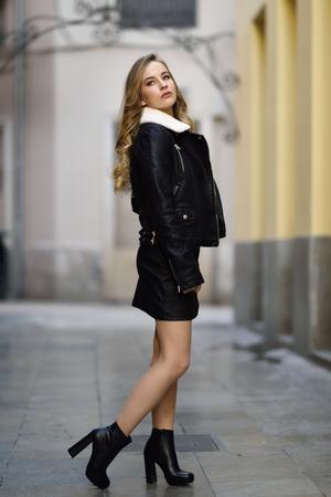 도시 배경에서 금발의 여자입니다. 아름 다운 젊은 여자 검은 가죽 자 켓과 거리에 서 서 미니 스커트 입고. 긴 물결 모양 머리 헤어 스타일 및 파란 눈