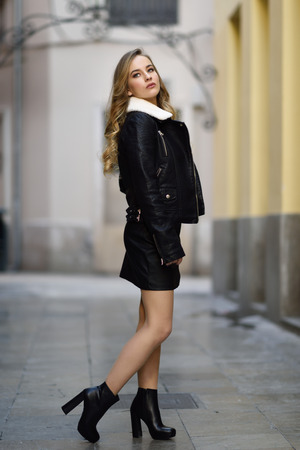Blonde woman in urban background. Beautiful young girl wearing black leather jacket and mini skirt standing in the street. Pretty russian female with long wavy hair hairstyle and blue eyes. Banque d'images