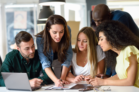 Five young people studying on white desk. Beautiful women and men working together wearing casual clothes. Multi-ethnic group. Stockfoto