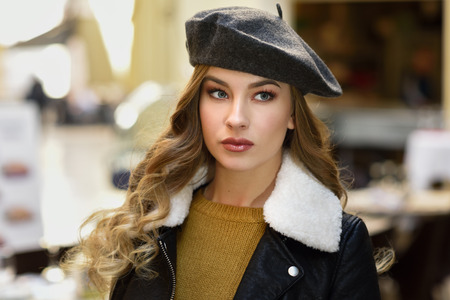 Blonde russian woman in urban background. Beautiful young girl wearing beret, black leather jacket and mini skirt standing in the street. Pretty female with long wavy hair hairstyle and blue eyes. Stock Photo