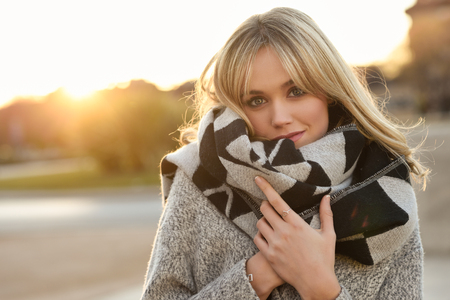 Attractive blonde woman in urban background with sun backlight. Young girl wearing winter coat and scarf standing in the street. Pretty female with straight hair hairstyle and blue eyes. Standard-Bild