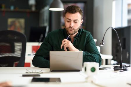 Joven estudiando con ordenador portátil en el escritorio blanco. Chico atractivo con barba vistiendo ropa casual.
