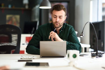 Young man studying with laptop computer on white desk. Attractive guy with beard wearing casual clothes.