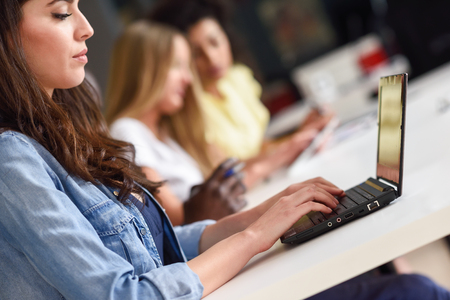 Young woman studying with laptop computer on white desk. Beautiful girls and guys working together wearing casual clothes. Multi-ethnic coworkers group. Stock Photo