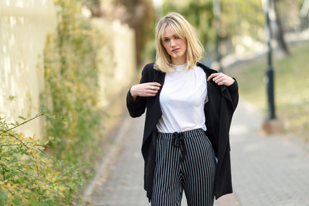 Beautiful blonde woman in urban background. Young girl wearing black blazer jacket and striped trousers standing in the street. Pretty female with straight hair hairstyle and blue eyes. Stock Photo