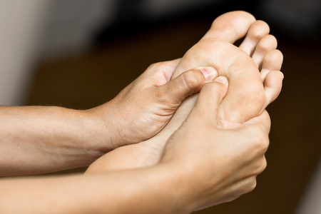 Medical massage at the foot in a physiotherapy center. Female physiotherapist inspecting her patient. Stockfoto