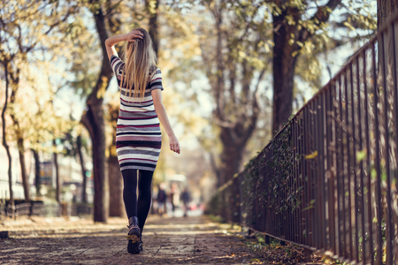 Young blonde woman walking in the street. Beautiful girl in urban background wearing striped dress and black tights. Female with straight hair. Back view