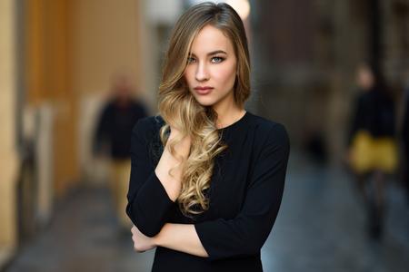 都市の背景に金髪の女性。美しい少女が通りに立っている黒のエレガントなドレスを着ています。長いウェーブのかかった髪の髪型と青目でプリテ 写真素材