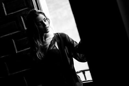 ランジェリー立って彼女の寝室の窓の近くでセクシーな若い女性。ブルネットの少女は、黒体とネグリジェを身に着けています。女性の下着。黒と白の写真。 写真素材 - 88029990