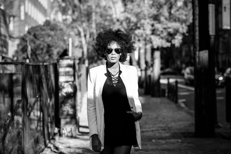 Young black woman with afro hairstyle standing in urban background with aviator sunglasses. Mixed girl wearing white jacket and black dress posing near a brick wall Stock Photo