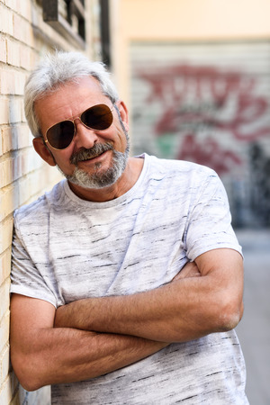 Mature man smiling at camera in urban background. Senior male with white hair and beard wearing casual clothes and aviator sunglasses. Stock Photo
