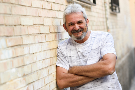 Mature man smiling at camera in urban background. Senior male with white hair and beard wearing casual clothes. Stock Photo