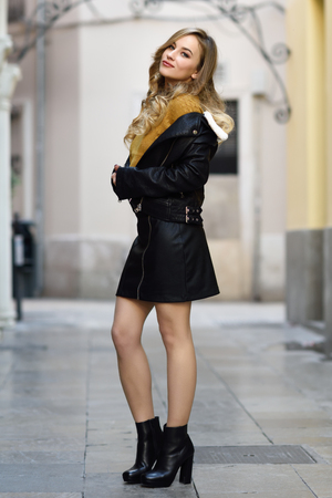 Blondevrouw die op stedelijke achtergrond glimlachen. Mooi jong meisje dat zwart leerjasje en minirok draagt die zich in de straat bevinden. Vrij Russisch wijfje met lang golvend haarkapsel en blauwe ogen.