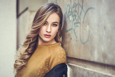 Blonde woman in urban background. Beautiful young girl wearing black leather jacket and mini skirt standing in the street. Pretty russian female with long wavy hair hairstyle and blue eyes. Foto de archivo