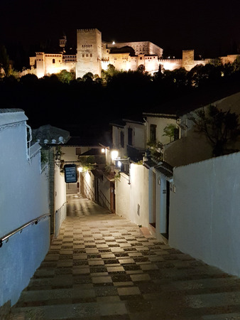 Night view of the famous Alhambra palace in Granada from a narrow street in Albaicin quarter, Spain