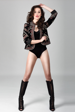 Attractive girl, model of fashion, wearing modern jacket, high boots and black lingerie. Female with long wavy hairstyle. Studio Shot.
