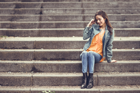 Young woman with nice hair wearing casual clothes in urban background. Happy girl with wavy hairstyle sitting in urban stairs.