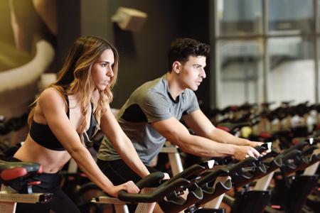 Deux personnes faisant du vélo dans la salle de sport, faisant de l?exercice pour les jambes faisant de l?entraînement cardio-cycliste. Couple dans une classe de spinning portant des vêtements de sport. Banque d'images