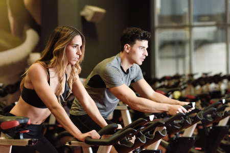 Due persone in bicicletta in palestra, che esercitano le gambe facendo bici cardio allenamento ciclismo. Coppia in una classe di spinning indossando abbigliamento sportivo. Archivio Fotografico