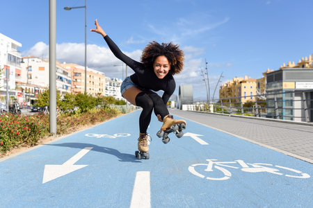 Young fit black woman on roller skates riding outdoors on bike line. Smiling girl with afro hairstyle rollerblading on sunny day 版權商用圖片 - 92880282
