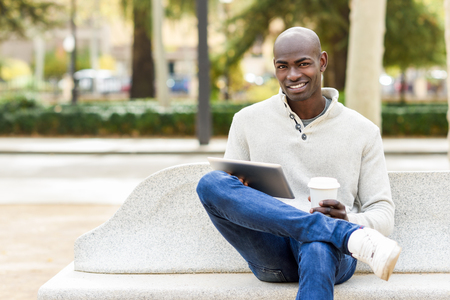 Black young man with tablet computer and take away coffee in urban background. Young african guy with shaved head wearing casual clothes.