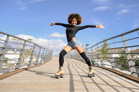 Donna di colore, acconciatura afro, sui pattini di rullo che guidano all'aperto sul ponte urbano con le braccia aperte. Giovane femmina sorridente che rollerblading il giorno soleggiato. Belle nuvole nel cielo.