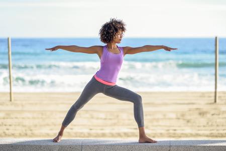 Femme noire, coiffure afro, faire du yoga en posture de guerrier à la plage. Jeune femme portant des vêtements de sport avec la mer à l'arrière-plan