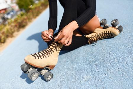 Close-up of black girl sitting on bike line and puts on skates. Unrecognizable woman. Rollerblading concept