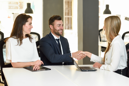 Smiling young couple shaking hands with an insurance agent or investment adviser. Three people meeting in an office reaching an agreement Stock Photo