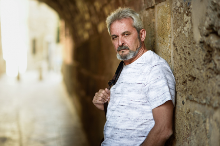 Portrait of a mature serious man in urban background. Senior male with white hair and beard wearing casual clothes.