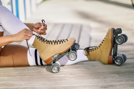 Close-up of black girl sitting on wooden floor puts on skates outdoors. Unrecognizable woman. Rollerblading concept