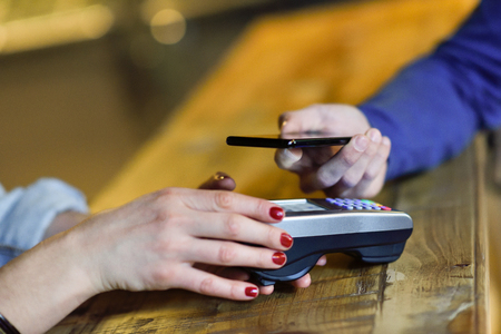 NFC Near Field Communication Mobile Payment. Hand holding smartphone paying on EDC machine. Stock Photo