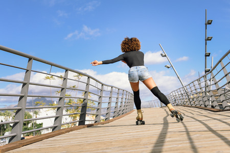 Rear view of black woman, afro hairstyle, on roller skates riding outdoors on urban bridge. Young girl rollerblading on sunny day. Stock Photo