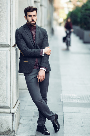 Young bearded man, model of fashion, standing in urban background wearing british elegant suit. Guy with beard and modern hairstyle in the street. Archivio Fotografico