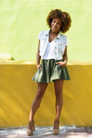 Young black woman, afro hairstyle, standing in the street. Girl wearing casual clothes smiling in urban background. Female with skirt, denim vest and high heels.