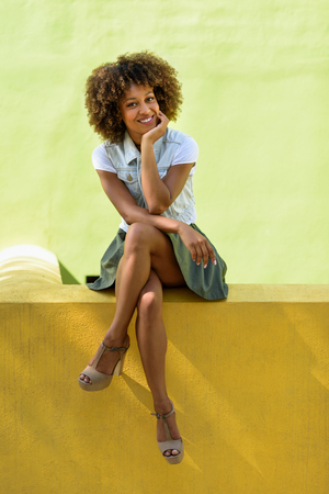 Young black woman, afro hairstyle, sitting on a wall smiling. Girl, model of fashion, wearing casual clothes in urban background. Female with skirt, denim vest and high heels. Foto de archivo