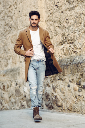 Young man wearing winter clothes in the street. Young bearded guy with modern hairstyle with coat, blue jeans and white t-shirt. Stock Photo