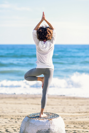 Rear view of young black woman doing yoga in the beach. Female wearing white sport clothes in tree asana with defocused sea background. Afro hairsytle.